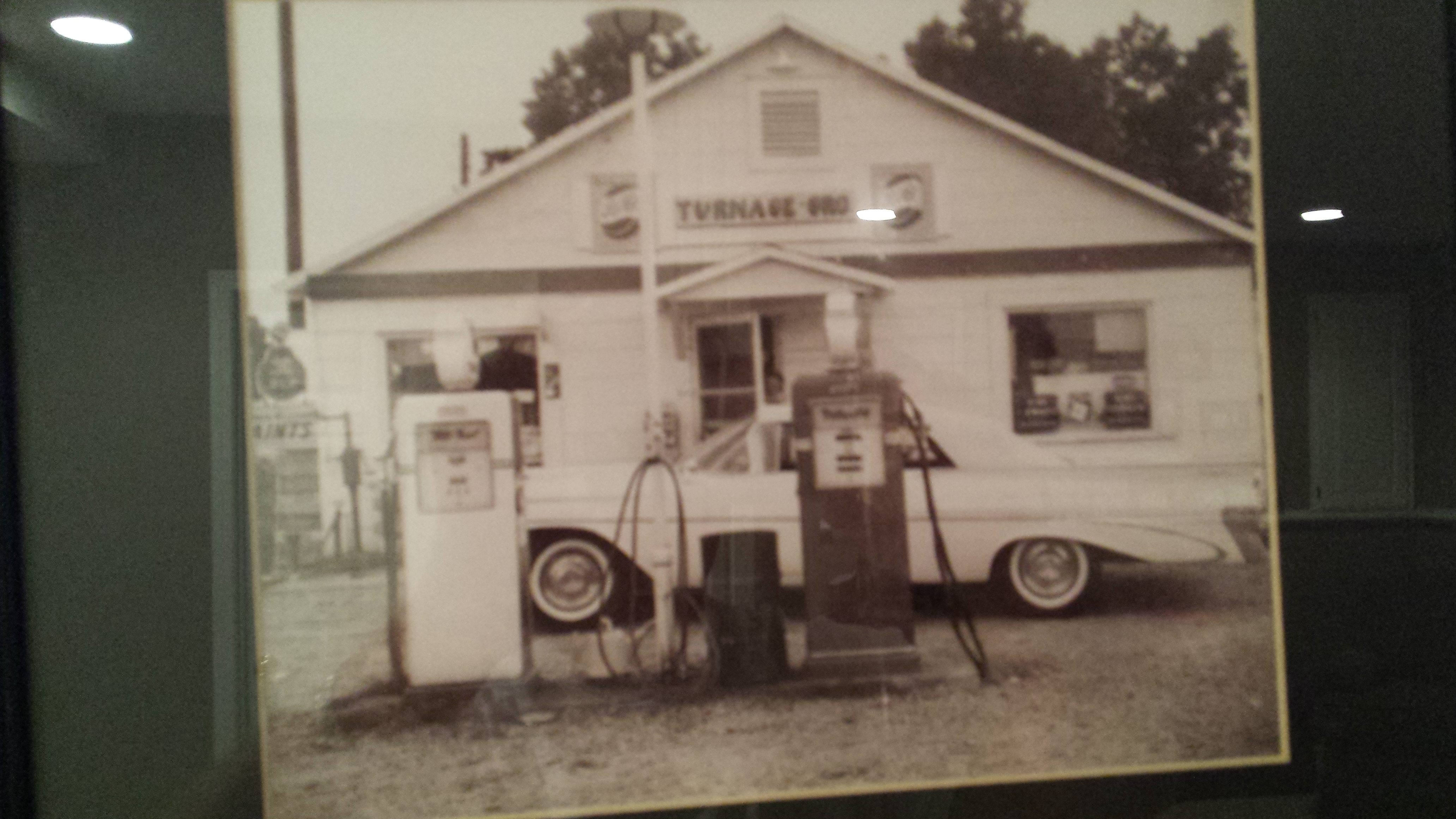 Vintage photo of small store with gas pump and classic car.